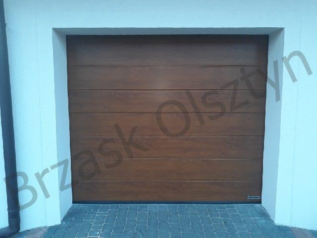 montaż bramy garażowej z przetłoczeniem M w okleinie Golden Oak - złoty dąb.