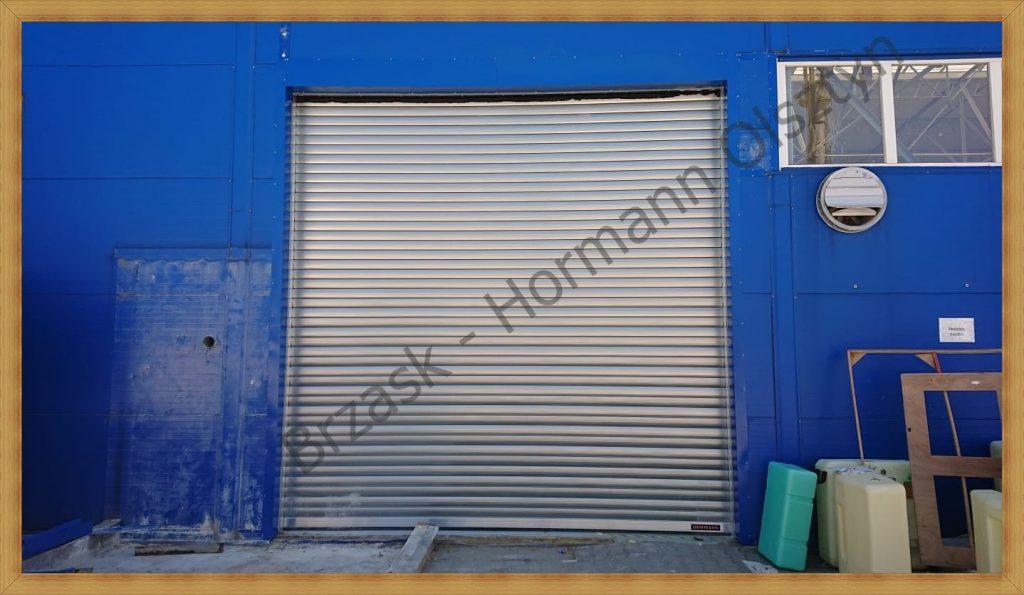 montaż przemysłowej bramy z przetłoczeniem S. Klient wybrał wariant kolorystyczny RAL9002 (biało-szare)